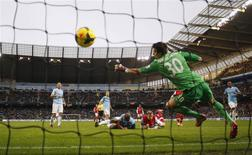 Arsenal's Per Mertesacker (C, bottom) heads and scores a goal during their English Premier League soccer match against Manchester City at the Etihad stadium in Manchester, northern England December 14, 2013. REUTERS/Phil Noble