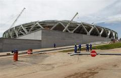 Workers stand outside the Arena Amazonia stadium under construction to host several 2014 World Cup soccer games, in Manaus December 14, 2013. REUTERS/Bruno Kelly