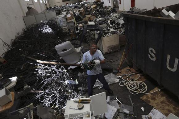 An employee holds circuit boards at the Coopermiti warehouse of electronic waste in Sao Paulo March 6, 2013. According to the United Nations Environment Programme (UNEP), Brazil generates the greatest amount of electronic waste (e-waste) per capita among emerging countries. REUTERS/Nacho Doce