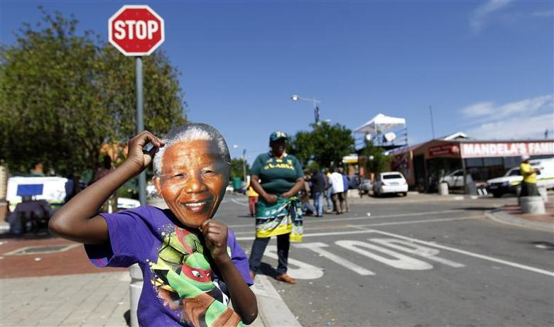 A boy wears a mask of former South African President Nelson Mandela outside his house along Vilakazi Street in Soweto, where Mandela resided when he lived in the township, December 15, 2013. REUTERS/Thomas Mukoya