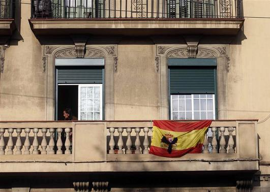 A black ribbon is seen on a Spanish flag at a balcony in Barcelona December 13, 2013. REUTERS-Albert Gea