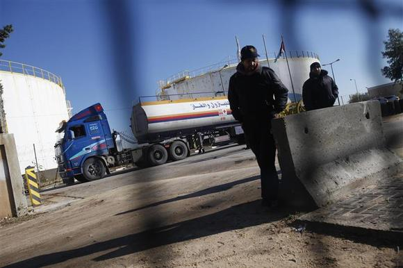 Palestinian policemen loyal to Hamas keep guard as a fuel tanker arrives to Gaza's power plant in the central Gaza Strip December 15, 2013. REUTERS/Ibraheem Abu Mustafa