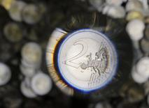 A two Euro coin is checked after being minted in the Austrian Mint (Muenze Oesterreich) headquarters in Vienna June 20, 2013. The Austrian mint was first mentioned in papers in 1371 and is located in Vienna. REUTERS/Leonhard Foeger