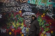 "Dimitar ""Mitko"" Todorov, a Roma from the Bulgarian city of Plevna, walks past a graffiti at a former ice factory that serves as his home in Berlin, December 5, 2013. REUTERS/Thomas Peter"