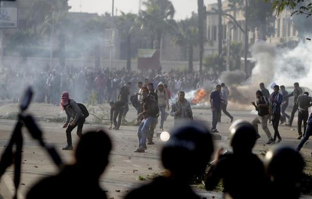 Cairo University students, who are supporters of the Muslim Brotherhood and ousted Egyptian President Mohamed Mursi, clash with riot police outside the university, in Cairo December 10, 2013. REUTERS/Mohamed Abd El Ghany