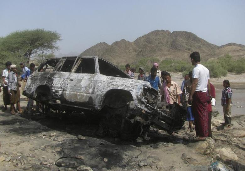 People gather at the site of a drone strike on the road between Yafe and Radfan districts of the southern Yemeni province of Lahj August 11, 2013. REUTERS/Stringer