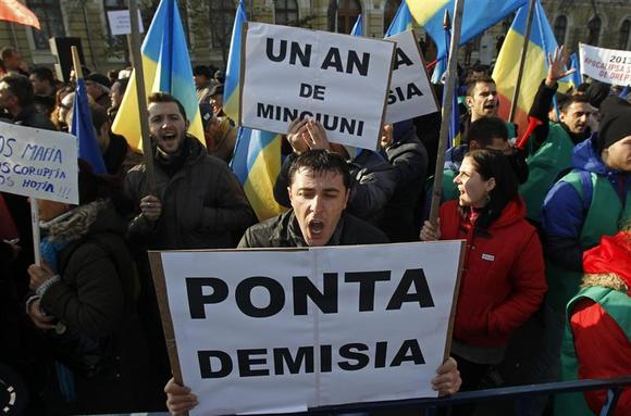 People shout slogans during a protest against a law that increases the immunity of parliament members, in front of Romania's government headquarters in Bucharest December 14, 2013. REUTERS/Bogdan Cristel