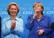German Labour Minister Ursula von der Leyen (L) and German Chancellor and leader of the Christian Democratic Union (CDU) Angela Merkel celebrate after first exit polls in the German general election (Bundestagswahl) at the CDU party headquarters in Berlin September 22, 2013. REUTERS/Kai Pfaffenbach