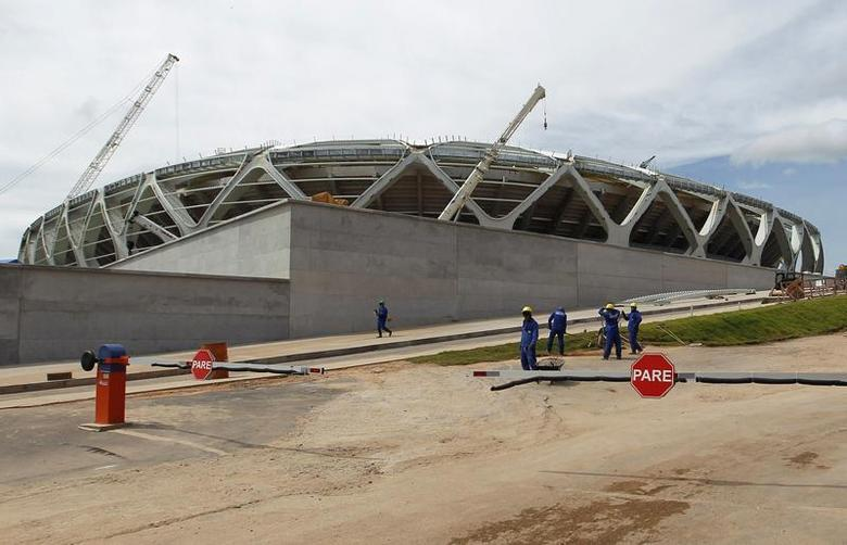 Workers stand outside the Arena Amazonia stadium under construction to host several 2014 World Cup football games, in Manaus December 14, 2013. REUTERS/Bruno Kelly