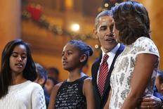 U.S. President Barack Obama (2nd R), his wife Michelle (R) and their daughters Malia (L) and Sasha (2nd L) join performers onstage to sing Christmas carols during a taping of the Christmas in Washington television benefit program at the National Building Museum in Washington December 15, 2013. REUTERS/Jonathan Ernst