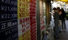 People look at the prices of tickets outside a ticket shop at the Ginza shopping district in Tokyo October 31, 2013. REUTERS/Yuya Shino