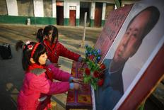 Students put plastic flowers next to a portrait of China's late chairman Mao Zedong at the Democracy Elementary and Middle School in Sitong town, Henan province December 4, 2013. REUTERS/Carlos Barria
