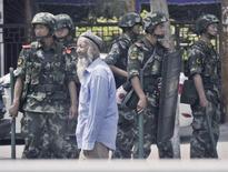 Полицейские охраняют рынок в Урумчи 29 июня 2013 года. Китайская полиция застрелила 14 участников беспорядков и потеряла двоих убитыми под городом Кашгар в населенном преимущественно мусульманами Синьцзян-Уйгурском автономном районе (СУАР), сообщили власти в понедельник. REUTERS/Kyodo