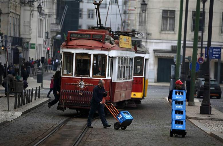 Men push crates of bottles of water near a tram in downtown Lisbon December 13, 2013. REUTERS/Rafael Marchante