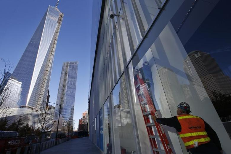 Workers put finishing touches on a window in the lobby of the soon to be opened 4 World Trade Center tower in New York, November 8, 2013. REUTERS/Mike Segar