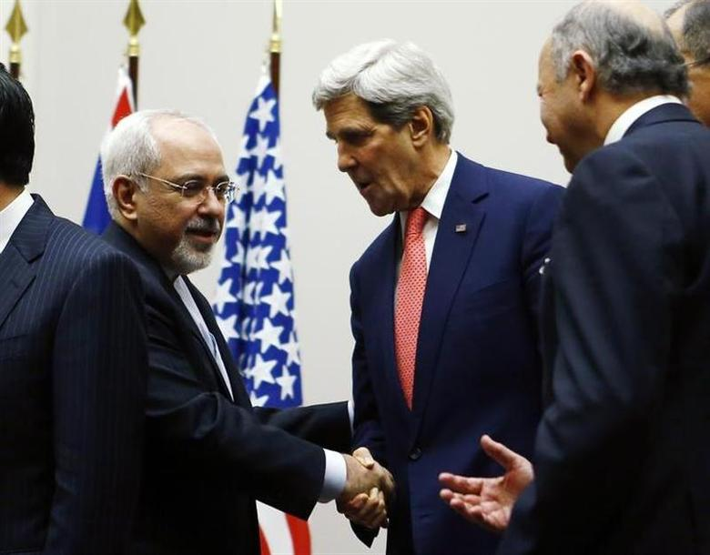 U.S. Secretary of State John Kerry (R) shakes hands with Iranian Foreign Minister Mohammad Javad Zarif after a ceremony at the United Nations in Geneva November 24, 2013. REUTERS/Denis Balibouse