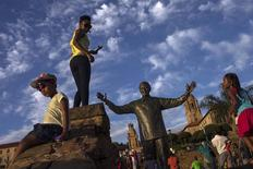 Visitors stand around a bronze statue of the late former South African President Nelson Mandela hours after it was unveiled as part of Day of Reconciliation celebrations at the Union Buildings in Pretoria December 16, 2013. REUTERS/Adrees Latif