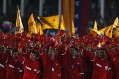 Trabajadores de PDVSA, saludan al presidente de Venezuela, Nicolás Maduro, en un desfile realizado en la Academia Militar de Caracas, abr 19 2013. Un cambio en el sistema tributario y una devaluación de la moneda venezolana impulsaron las finanzas de la estatal Petróleos de Venezuela (PDVSA) durante la primera mitad del año, en momentos en que la firma recortó sus gastos operacionales y sociales luego de fuertes desembolsos en el año electoral del 2012. REUTERS/Tomas Bravo