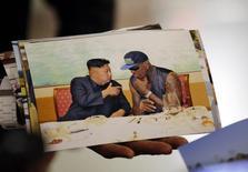 Бывший баскетболист Деннис Родман показывает свою фотографию с лидером КНДР Ким Чен Ыном в аэропорту Пекина 7 сентября 2013 года. Звезда баскетбола Деннис Родман в четверг в третий раз поедет в Северную Корею, несмотря на политическую напряженность, возникшую после казни дяди лидера КНДР Ким Чен Ына. REUTERS/Kim Kyung-Hoon