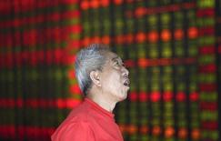 Инвестор смотрит на табло брокерской конторы в Шеэньяне, КНР 16 августа 2013 года. Азиатские фондовые рынки завершили торги вторника разнонаправленно в ожидании итогов совещания ФРС, которые будут объявлены после закрытия азиатских рынков в среду. REUTERS/Stringer