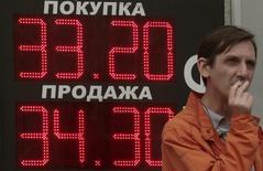 Мужчина курит у вывески пункта обмена валюты в Москве 1 июня 2012 года. Рубль во вторник днем торгуется с небольшими изменениями в ожидании итогов заседания ФРС, от которого зависит последующее отношение к рискованным активам. REUTERS/Sergei Karpukhin