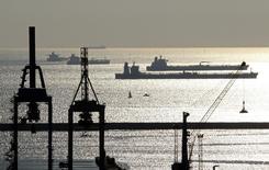 Нефтяные и газовые танкеры стоят на якоре в бухте Марселя 27 октября 2010 года. Цены на нефть снижаются накануне совещания ФРС, на котором центробанк может принять решение о сокращении стимулов. REUTERS/Jean-Paul Pelissier