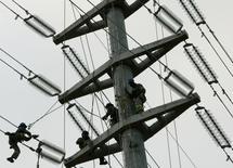 Trabalhadores instalam linhas de energia elétrica no canteiro de obras da ponte Octavio Frias de Oliveira em São Paulo. A Agência Nacional de Energia Elétrica (Aneel) reconheceu parcialmente o recurso da Eletropaulo sobre o terceiro ciclo de revisão tarifária, permitindo elevação na base de remuneração líquida da companhia de 4,4 bilhões para 4,67 bilhões de reais. 20/02/2008 REUTERS/Paulo Whitaker
