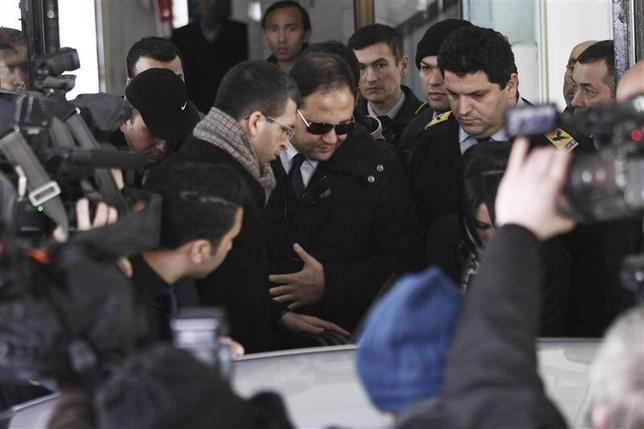Baris Guler (C in sunglasses), son of Turkey's Interior Minister Muammer Guler, is escorted by plainclothes police officers as he leaves a medical check-up in Istanbul December 16, 2013. REUTERS/Kursat Bayhan/Zaman Daily via Cihan News Agency