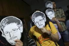 Люди в масках с изображением Эдварда Сноудена перед посвященными американской слежке слушаниями в бразильском конгрессе в Бразилиа 6 августа 2013 года. Бывший подрядчик американских спецслужб Сноуден, получивший временное убежище в России, попросил постоянного у Бразилии, пообещав помочь ей в расследовании слежки, устроенной за латиноамериканцами Агентством национальной безопасности США. REUTERS/Ueslei Marcelino