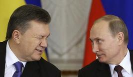 Президенты Украины и России Виктор Янукович и Владимир Путин на подписании совместных документов после переговоров в московском Кремле 17 декабря 2013 года. Путин пообещал помочь охваченной массовыми антиправительственными выступлениями и финансовым кризисом Украине, заявив о готовности потратить $15 миллиардов из Фонда национального благосостояния, подушки стабильности для российских пенсионеров. Украинская оппозиция назвала Януковича предателем национальных интересов. REUTERS/Sergei Karpukhin