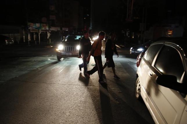 People walk on a street during a blackout in Caracas December 2, 2013. REUTERS/Carlos Garcia Rawlins