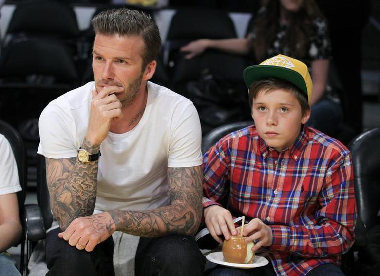 Soccer star David Beckham (L) and his son Brooklyn watch the Los Angeles Lakers play the Miami Heat in their NBA basketball game in Los Angeles, California March 4, 2012. REUTERS/Lucy Nicholson