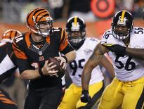 Cincinnati Bengals quarterback Andy Dalton (14) throws under pressure from the Pittsburgh Steelers' LaMarr Woodley (56) and Jarvis Jones (95) during the second half of play in their NFL football game at Paul Brown Stadium in Cincinnati, Ohio, September 16, 2013. REUTERS/John Sommers II
