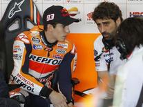 Honda MotoGP rider Marc Marquez (L) of Spain listens to technicians before the first free practice session ahead the Valencia Motorcycle Grand Prix at the Ricardo Tormo racetrack in Cheste, near Valencia, November 8, 2013. REUTERS/Heino Kalis