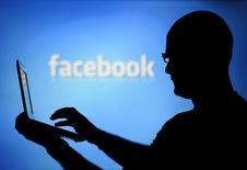 Силуэт мужчины с ноутбуком на фоне экрана с логотипом Facebook в городе Зеница 14 августа 2013 года. Facebook Inc приступил к тестированию автоматически проигрывающейся видеорекламы, аккуратно приоткрывая новый источник прибыли, опасный тем, что он может раздражать самих пользователей. REUTERS/Dado Ruvic