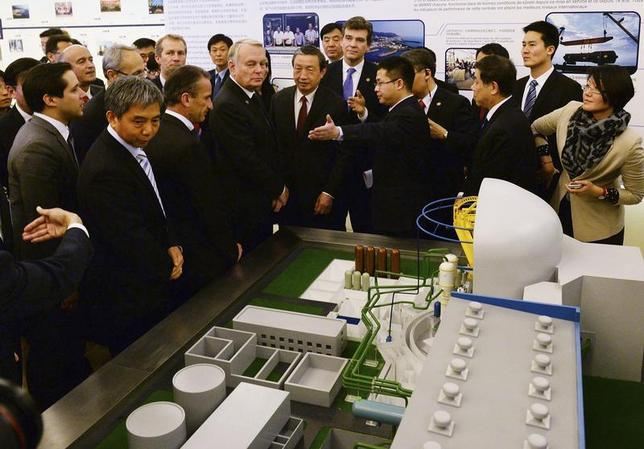 French Prime Minister Jean-Marc Ayrault (centre L) looks at a model of a power station during a Chinese-French forum on 30 years of nuclear cooperation, in the Great Hall of the People in Beijing December 6, 2013. REUTERS/Mark Ralston/ Pool