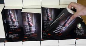 """Покупатель берет книгу Стига Ларссона в мадридском магазине 18 июня 2009 года. Шведский писатель Давид Лагеркранц напишет продолжение ставшей блокбастером трилогии покойного Стига Ларссона """"Миллениум"""", сообщило во вторник издательство Norstedts. REUTERS/Susana Vera"""