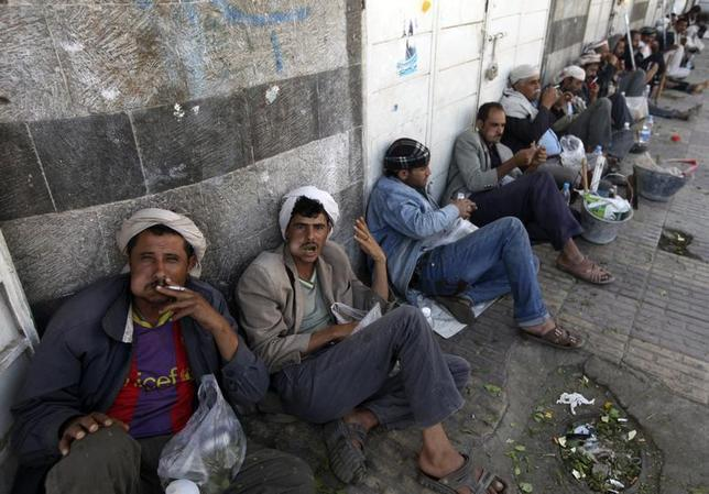 Men waiting to be hired for their labour, chew the mild stimulant qat as they sit along a main street in Sanaa November 3, 2013. REUTERS/Mohamed al-Sayaghi