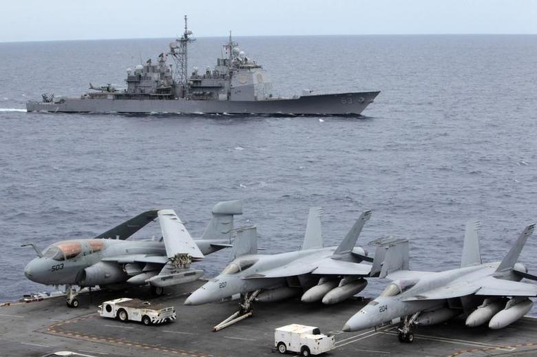 U.S fighter jets on standby at the upper deck of a USS George Washington aircraft carrier while a U.S. Cowpens ship pass during a media tour at the South China Sea, 170 nautical miles from Manila September 3, 2010. REUTERS/Romeo Ranoco