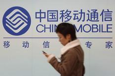 Uma mulher olha para a tela de seu celular enquanto passa em frente ao logotipo da China Mobile no centro de Xangai. A China Mobile disse que ainda está em negociações com a Apple para vender iPhones em meio a uma crescente especulação no setor de que as empresas estão prestes a anunciar um acordo que deve dar à gigante de tecnologia milhões de novos clientes em potencial. 18/12/2013 REUTERS/Aly Song