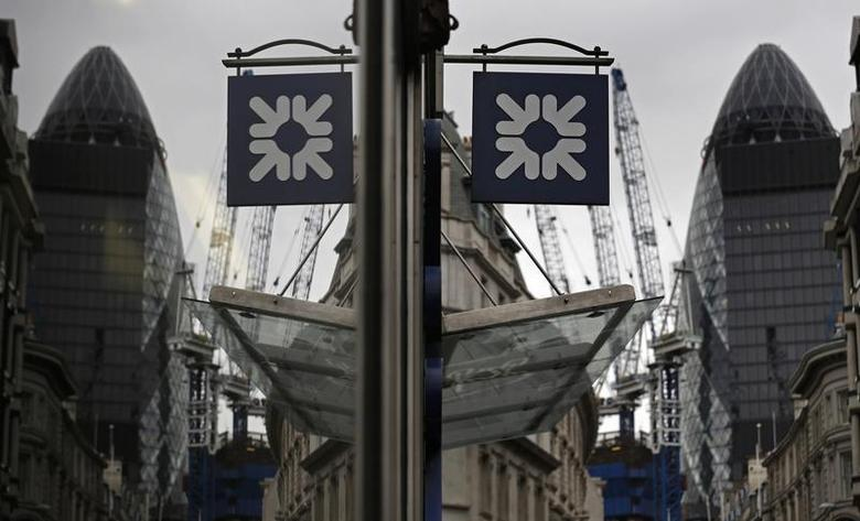 A logo of the Royal Bank of Scotland (RBS) is reflected in the window of a branch office in London November 1, 2013. REUTERS/Luke MacGregor