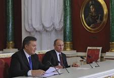 Le président ukrainien Viktor Ianoukovitch et son homologue russe Vladimir Poutine à Moscou. Alors que les manifestations antigouvernementales se poursuivent à Kiev, le Premier ministre ukrainien, Mikola Azarov, a salué mercredi le plan d'aide financière de 15 milliards de dollars accordé par la Russie à l'Ukraine. /Photo prise le 17 décembre 2013/REUTERS/Michael Klimentyev/RIA Novosti