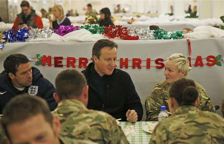 Britain's Prime Minister David Cameron (C) eats breakfast with British soldiers at Camp Bastion, outside Lashkar Gah, in Helmand province, southern Afghanistan December 16, 2013. REUTERS/Lefteris Pitarakis/Pool