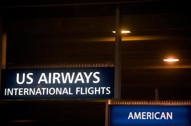 US Airways and American Airlines signs are pictured at Philadelphia International Airport in Philadelphia, Pennsylvania on December 9, 2013. REUTERS/Mark Makela