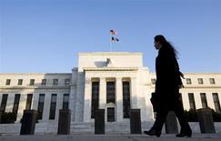 La Réserve fédérale (Fed) va réduire son programme de rachats mensuels d'actifs mais a compensé cette mesure attendue de longue date en laissant entendre qu'elle maintiendrait ses taux directeurs à un bas niveau pour une période plus longue encore qu'elle ne s'y était engagée. La banque centrale américaine va réduire ses achats d'actifs de 10 milliards de dollars par mois à 75 milliards, avec une baisse dans les mêmes proportions en titres adossés à des créances hypothécaires (MBS) et en bons du Trésor. /Photo d'archives/REUTERS/Larry Downing
