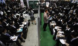 Job seekers listen to presentations by company employees during a job fair held for fresh graduates in Tokyo December 7, 2013. REUTERS/Yuya Shino