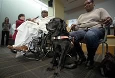 Blind man Cecil Williams (L) speaks about his service dog Orlando as his partner Cynthia holds the leash during a press conference in New York December 18, 2013. REUTERS/Carlo Allegri