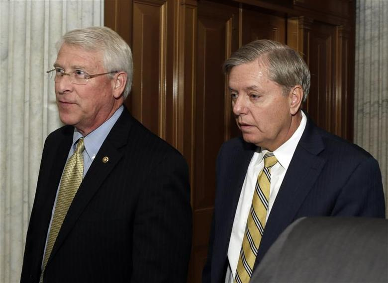Senators Roger Wicker (R-MS) (L) and Lindsey Graham (R-SC) walk into the Senate chamber to vote on the U.S. budget bill in Washington December 18, 2013.REUTERS/Gary Cameron