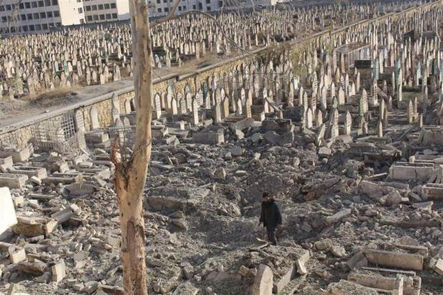 A man walks through a graveyard that was damaged by what activists said was shelling from forces loyal to Syria's President Bashar al-Assad in the Kadi Askar neighbourhood of Aleppo, December 14, 2013. REUTERS/Mahmoud Hebbo