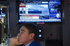 Трейдеры следят за новостями о решении ФРС в зале Нью-Йоркской фондовой биржи 18 декабря 2013 года. Федеральная резервная система США объявила о сокращении агрессивной скупки активов, направленной на снижение стоимости заимствований, но пообещала удерживать процентные ставки около нуля на протяжении длительного периода. REUTERS/Lucas Jackson